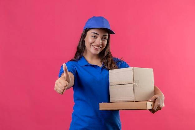 Junges liefermädchen in der blauen uniform und in der kappe, die pappkartons hält, die fröhlich daumen zeigen, die über rosa hintergrund stehen