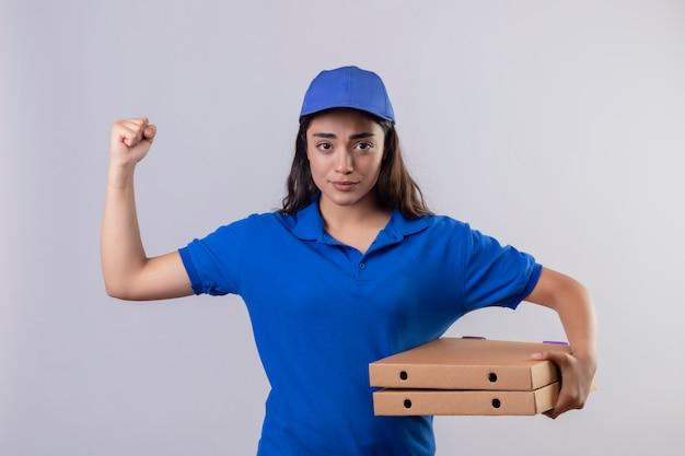 Junges liefermädchen in der blauen uniform und in der kappe, die pizzakästen anheben, die faust betrachten kamera mit stirnrunzelndem gesicht stehen über weißem hintergrund betrachten