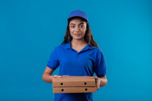 Junges liefermädchen in der blauen uniform und in der kappe, die pizzakästen betrachten, die kamera betrachten, die zuversichtlich glücklich und positiv steht über blauem hintergrund