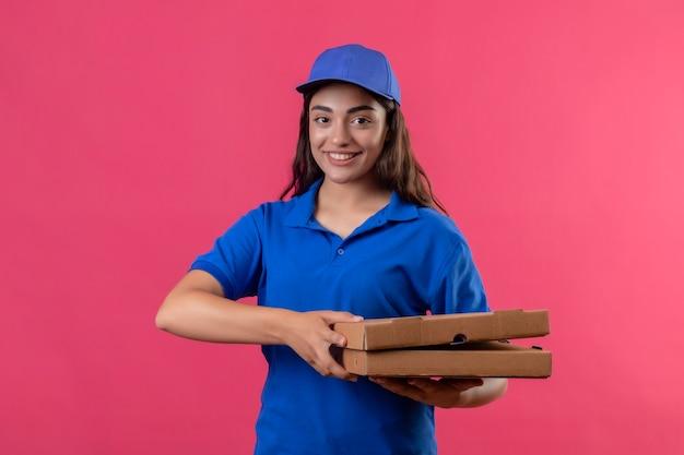 Junges liefermädchen in der blauen uniform und in der kappe, die pizzakästen betrachten, die kamera betrachten, die zuversichtlich glücklich und positiv steht über rosa hintergrund