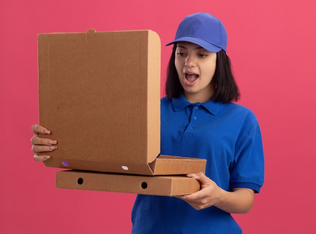 Junges liefermädchen in der blauen uniform und in der kappe, die pizzaschachteln hält, die eine offene schachtel betrachten, überrascht und überrascht, über rosa wand stehend