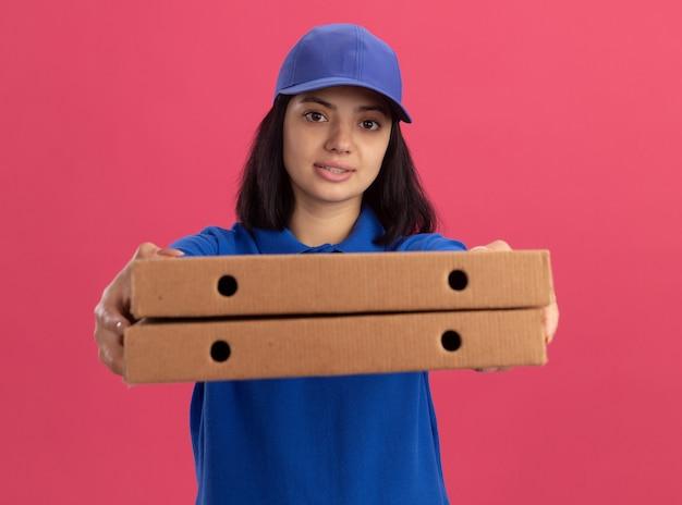 Junges liefermädchen in der blauen uniform und in der kappe, die pizzaschachteln hält, die sicher aussehend stehen über rosa wand strecken