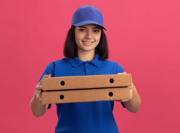 Junges liefermädchen in der blauen uniform und in der kappe, die pizzaschachteln lächelnd mit glücklichem gesicht stehen über rosa wand halten