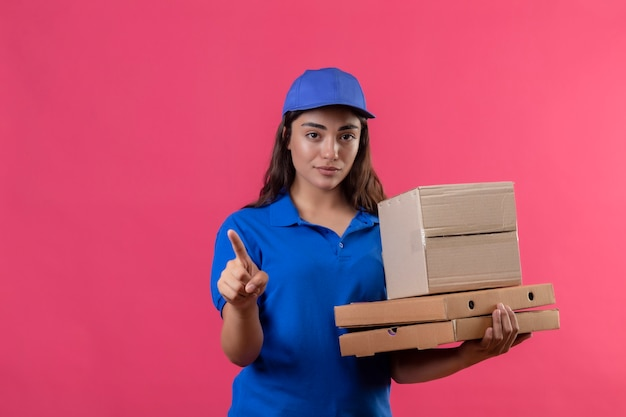 Junges liefermädchen in der blauen uniform und in der kappe, die pizzaschachteln und kastenverpackung hält, zeigt mit dem finger auf etwas, das kamera mit sicherem ausdruck über rosa hintergrund steht