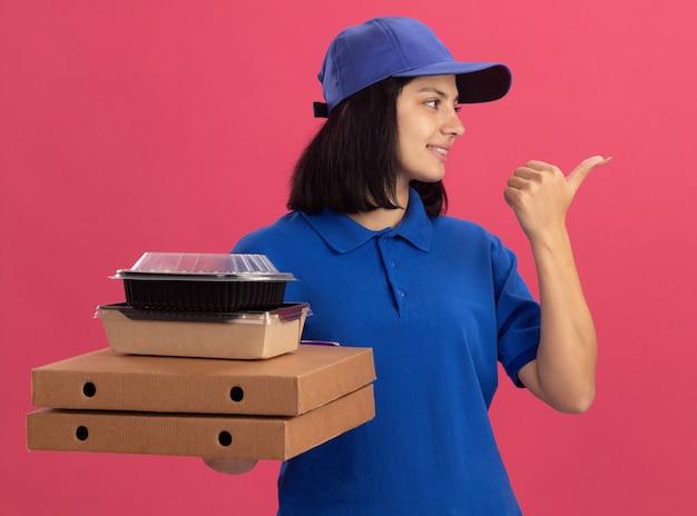 Junges liefermädchen in der blauen uniform und in der kappe, die pizzaschachteln und lebensmittelpaket lächelnd zeigt, zeigt mit daumen zur seite, die über rosa wand steht