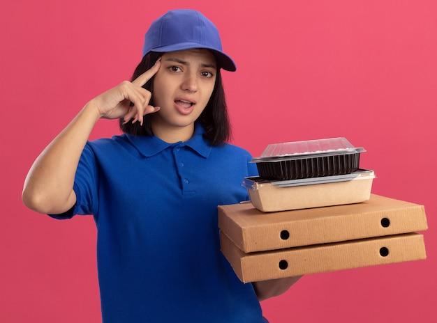 Junges liefermädchen in der blauen uniform und in der kappe, die pizzaschachteln und nahrungsmittelpaket hält, zeigt mit zeigefinger auf tempel, der verwirrt schaut, vergessen, über rosa wand zu stehen