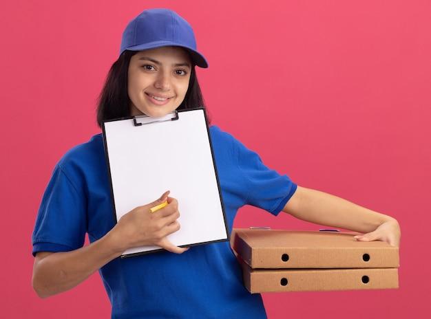 Junges liefermädchen in der blauen uniform und in der kappe, die pizzaschachteln und zwischenablage mit leeren seiten hält, die auf unterschrift warten, die über rosa wand steht