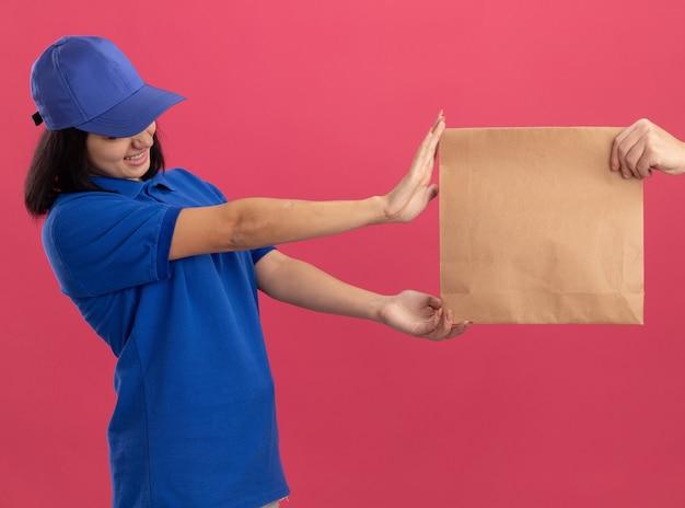 Junges liefermädchen in der blauen uniform und in der kappe, die sich weigern, ein papierpaket zu nehmen, das über rosa wand steht