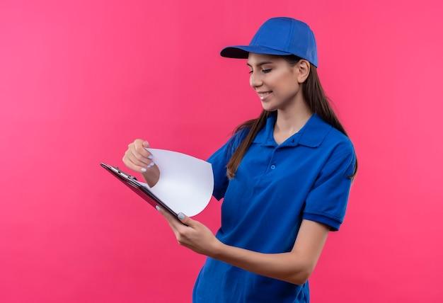 Junges liefermädchen in der blauen uniform und in der kappe, die zwischenablage hält, die leere seiten mit lächeln auf gesicht betrachtet