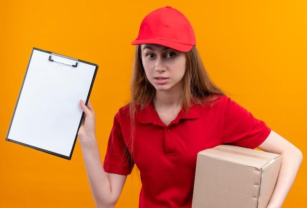 Junges liefermädchen in der roten uniform, die box hält und zwischenablage auf isolierter orange wand zeigt