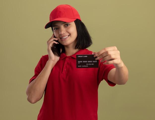 Junges liefermädchen in der roten uniform und in der kappe, die auf handy spricht, die kreditkarte zeigt, die fröhlich über lichtwand steht