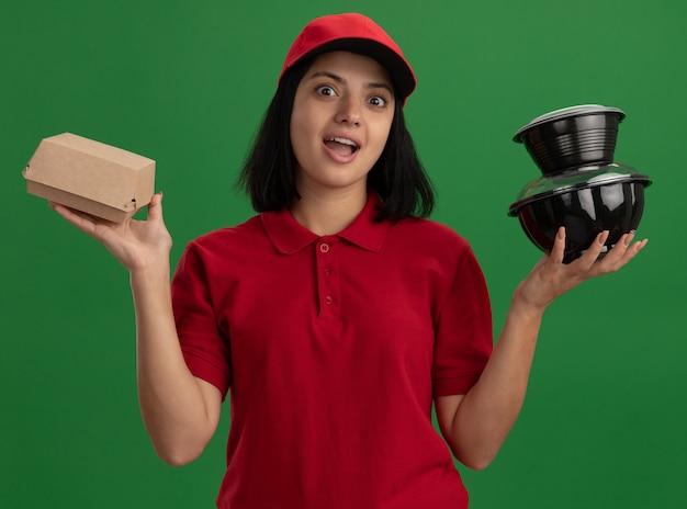 Junges liefermädchen in der roten uniform und in der kappe, die glückliche und überraschte lebensmittelpakete hält, die über grüner wand stehen
