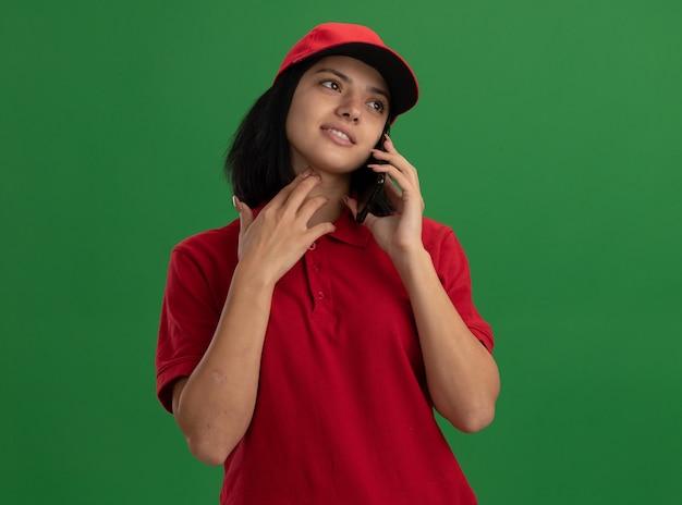 Junges liefermädchen in der roten uniform und in der kappe, die lächeln, während auf mobiltelefon stehen über grüner wand sprechen