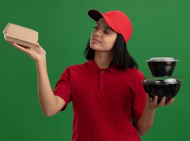 Junges liefermädchen in der roten uniform und in der kappe, die lebensmittelpakete hält, die zuversichtlich lächelnd über grüner wand stehen