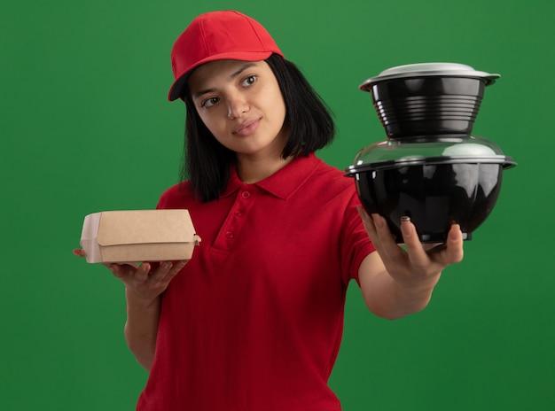 Junges liefermädchen in der roten uniform und in der kappe, die lebensmittelpakete halten, die zuversichtlich stehen über grüner wand stehen