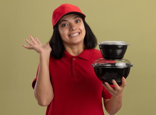 Junges liefermädchen in der roten uniform und in der kappe, die lebensmittelpakete lächelnd winkend mit der hand stehen über heller wand hält