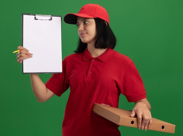 Junges liefermädchen in der roten uniform und in der kappe, die pizzaschachtel und zwischenablage mit bleistift hält, der es mit lächeln auf gesicht betrachtet, das über grüner wand steht