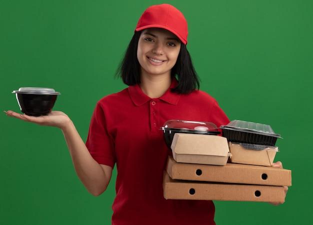 Junges liefermädchen in der roten uniform und in der kappe, die pizzaschachteln und nahrungsmittelpakete mit lächeln auf gesicht halten, das über grüner wand steht