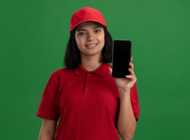 Junges liefermädchen in der roten uniform und in der kappe, die smartphone mit lächeln auf gesicht über grüner wand stehend zeigt