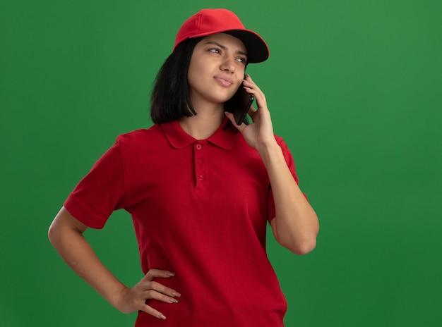 Junges liefermädchen in der roten uniform und in der kappe, die verwirrt und ängstlich schauen, während sie auf handy sprechen, das über grüner wand steht
