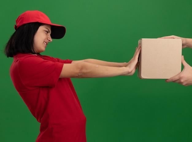 Junges liefermädchen in roter uniform und kappe, die sich weigern, ein papierpaket zu nehmen, das über grüner wand steht