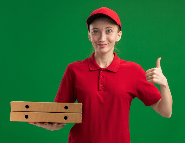 Junges liefermädchen in roter uniform und mütze, das pizzakartons hält und selbstbewusst lächelt und daumen nach oben über grüner wand zeigt