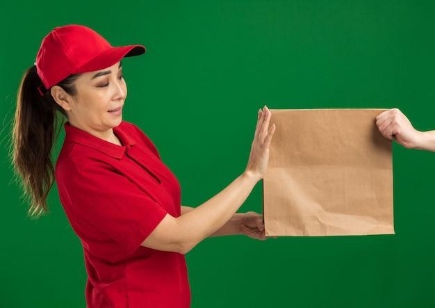 Junges liefermädchen in roter uniform und mütze, das sich weigert, ein papierpaket zu erhalten