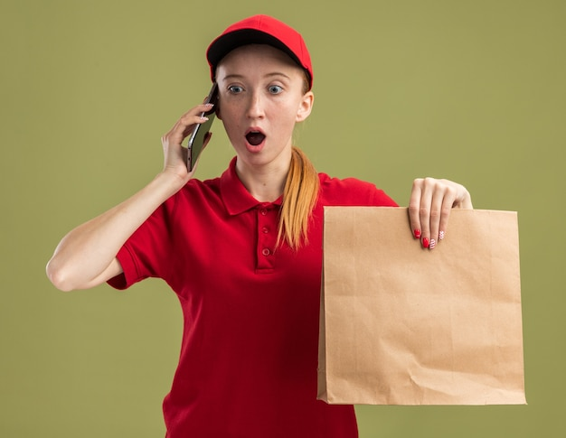 Junges liefermädchen in roter uniform und mütze mit papierpaket, das überrascht aussieht, während es über grüne wand telefoniert