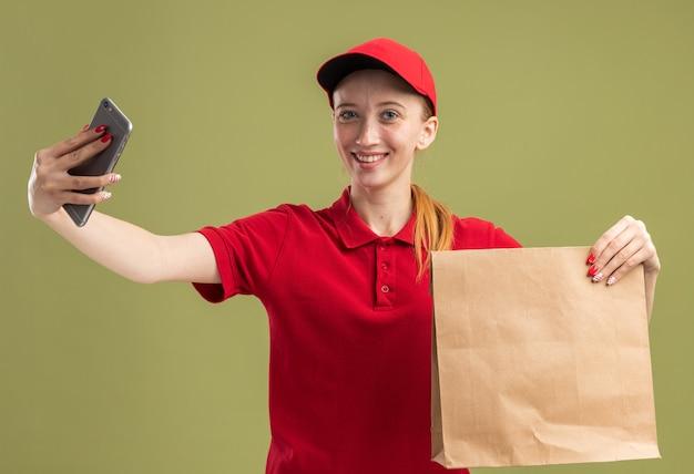 Junges liefermädchen in roter uniform und mütze mit papierpaket macht selfie mit smartphone und lächelt fröhlich über grüner wand