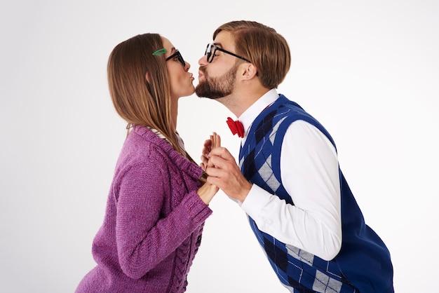 Junges lustig aussehendes geek-paar, das isoliert küsst