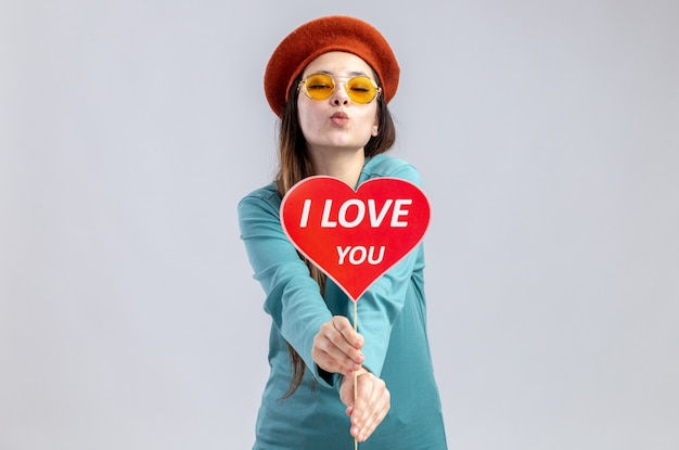 Junges mädchen am valentinstag mit hut mit brille, das rotes herz auf einem stock hält, mit dem ich dich liebe text in die kamera zeigt kussgeste isoliert auf weißem hintergrund