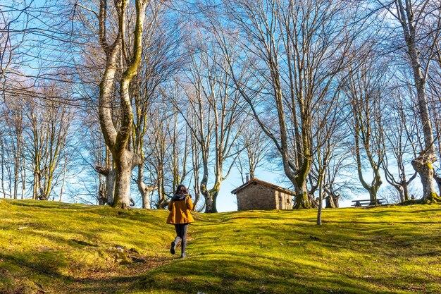 Junges mädchen auf dem wanderweg im buchenwald von oianleku und im zufluchtshaus im hintergrund, in der stadt oiartzun, gipuzkoa. baskenland. spanien