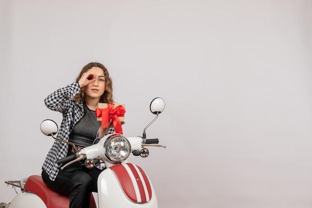 Junges mädchen auf moped, das geschenk hält, das handfernglas auf grauem macht