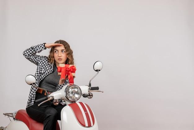 Junges mädchen auf moped mit geschenk auf grau