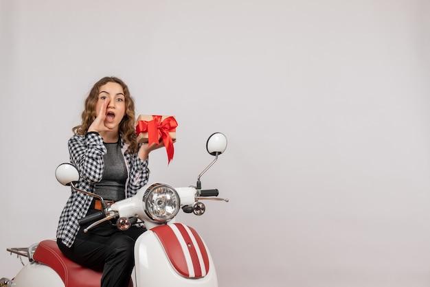 Junges mädchen auf moped mit geschenk, das jemanden auf grau anruft