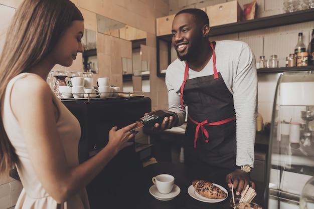 Junges mädchen berechnet das café per kreditkarte