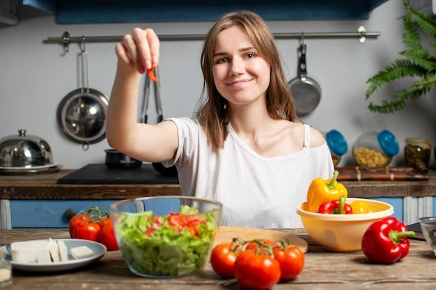 Junges mädchen bereitet einen vegetarischen salat in der küche zu, sie fügt geschnittene zutaten zum teller hinzu, der prozess der zubereitung gesunder lebensmittel
