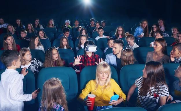 Junges mädchen, das 3d-brillen in der kinohalle aufpasst.