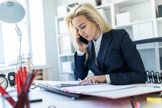 Junges mädchen, das am schreibtisch im büro sitzt, am telefon spricht und dokumente betrachtet.