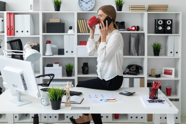 Junges mädchen, das am schreibtisch im büro sitzt, eine rote schale in ihrer hand hält und am telefon spricht