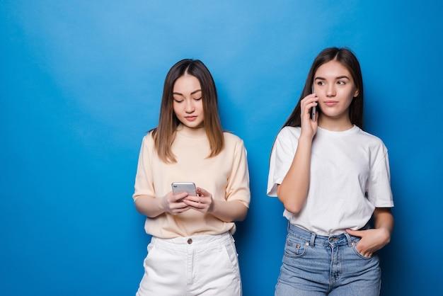 Junges mädchen, das am telefon spricht, und ein anderes mädchen benutzen telefon an einer blauen wand