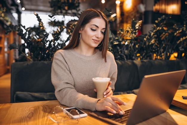 Junges mädchen, das an einem computer in einem café arbeitet