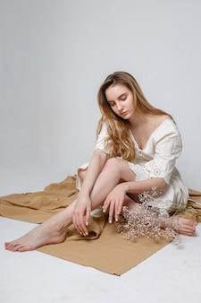 Junges mädchen, das auf boden auf dem beige gewebe lokalisiert auf weißem hintergrund sitzt. attraktives weibliches modell, das tief denkt.
