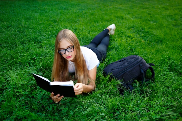 Junges mädchen, das auf dem gras im park liegt, buch studiert oder hausarbeit tut
