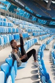 Junges mädchen, das auf dem sitz im stadion sitzt.