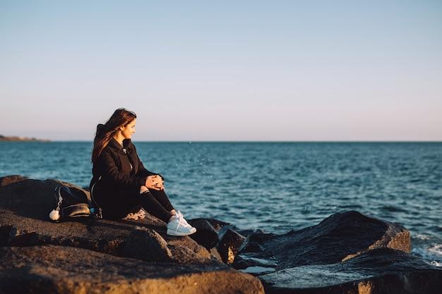 Junges mädchen, das auf den steinen am meer sitzt und den sonnenuntergang betrachtet.