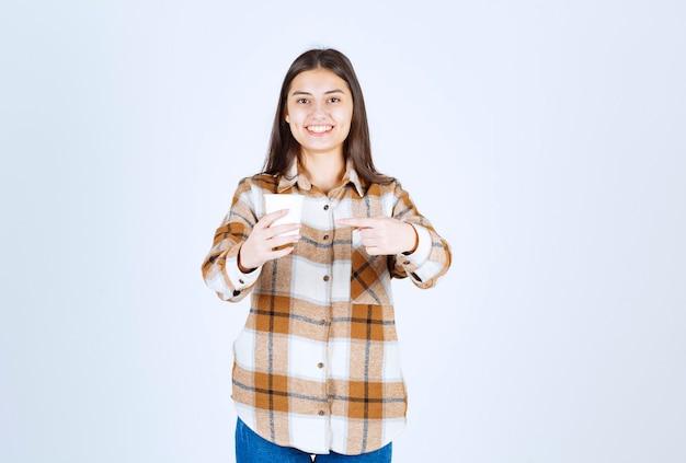 Junges mädchen, das auf eine tasse tee zeigt, die ein ok-zeichen auf der weißen wand gibt.