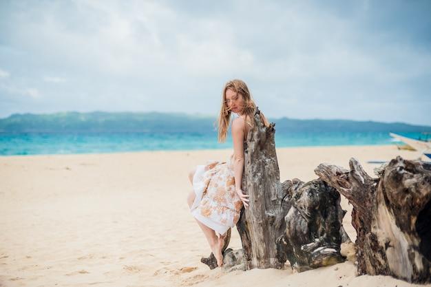 Junges mädchen, das auf einem alten baum am strand von boracay sitzt