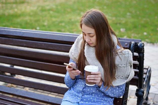 Junges mädchen, das auf einer bank im herbstpark sitzt, der kaffee trinkt und auf smartphone spricht
