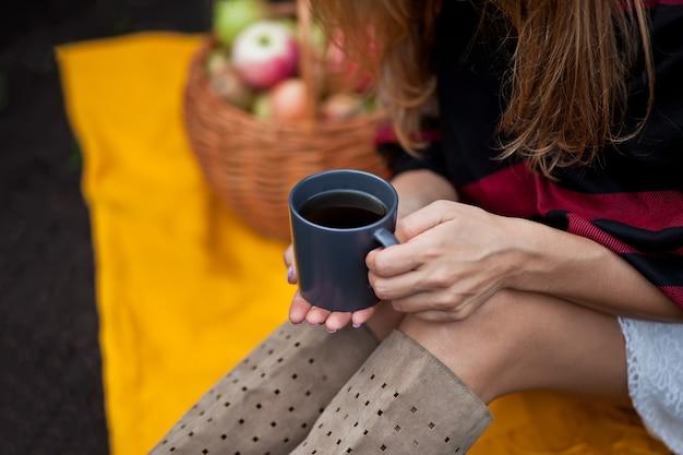 Junges mädchen, das auf einer gelben decke sitzt und becher heißen kaffee in einer hand hält